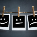 Happy sad and neutral emoticons on instant print-transfer-photographs-hanging on a clothesline