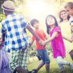 Groupe d'enfants se tenant par la main et souriant en jouant dehors.