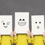 Cinq personnes portant des chemises jaunes, se tenant côte à côte et tenant des papiers blancs devant leur visage. Des émotions différentes sont dessinées sur les feuilles de papier.