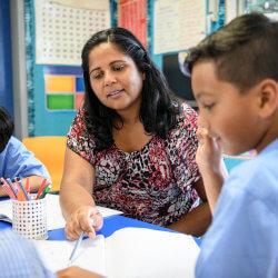 Une enseignante et un élève sont assis à une table. En se servant d'un crayon sur une feuille de travail, elle montre quelque chose à ce garçon.