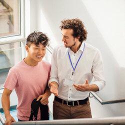 Un enseignant et un élève parlent ensemble en montant l'escalier de l'école.