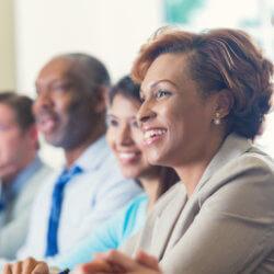 Un groupe diversifié de leaders scolaires écoute un animateur lors d'une réunion.