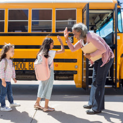School principal standing in front of a line of elementary students who are boarding a school bus and giving high fives.