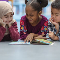 Three young children laying on the stomachs in the library looking at a book together.