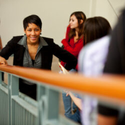 A smiling school principal is surrounded by out-of-focus students while walking up the stairs within a high school.