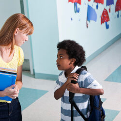 A principal carrying folders has stopped to talk with an elementary student in a well-lit school hallway. The student has a backpack over one shoulder and is making eye contact with the principal.