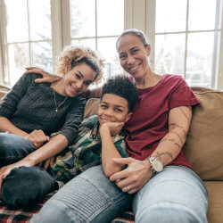 Same-sex parents and their child with their arms around eachother sitting on a beige couch in front of a sunny window. They're smiling at the camera.