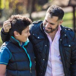 Un père et son fils se promènent dans un parc. Le père a son bras sur l'épaule de son fils alors que les deux se parlent et se sourient.