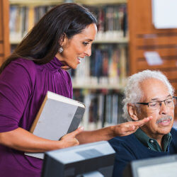 A group of staff are in a schoo library one is sitting in front of a computer and another stands beside them. They're looking at the screen and having a conversation.