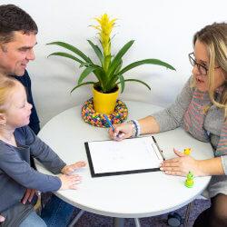 Une professionnelle de la santé mentale en milieu scolaire parle avec un père et sa fille. Les trois sont assis autour d'une table.