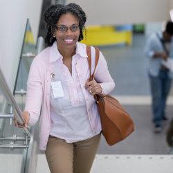 Une professionnelle de la santé mentale en milieu scolaire monte l'escalier, en souriant pour la caméra.