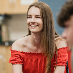 A teenager wearing a bright red shirt is smiling and appears to be listening to someone explain something. They're in a group in a room in a school.