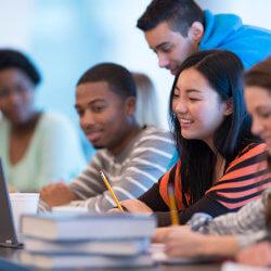 Des adolescents sont assis en train d'étudier. Leurs livres sont ouverts sur la table. Un élève regarde l'écran de son ordinateur portable.