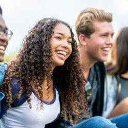 Un groupe d'élèves souriants sont assis à l'extérieur. Ils semblent être en train d'écouter quelqu'un qui raconte une histoire.