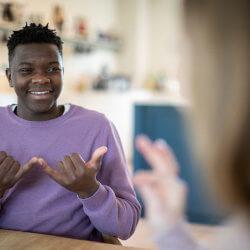 Un garçon communique avec une fille au moyen d'un langage gestuel.