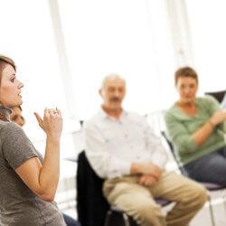 Des membres du personnel scolaire sont assis en cercle dans une salle, en train d'écouter une directrice d'école qui anime une discussion.