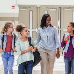 Une directrice d'école marchent dans le corridor avec trois élèves, l'une à sa droite et les deux autres à sa gauche. La directrice pose sa main sur le dos de celle qui est à sa gauche et en même temps elle sourit à l'élève à sa droite, qui lui parle. Derrière ce groupe il y a les portes de d'école.
