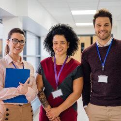 Dans le corridor de l'école, trois membres souriants du personnel scolaire se tiennent debout les uns à côté des autres pour se faire photographier. Autour du cou chacun porte une carte d'identification attachée à un cordon. La femme situé à la gauche de l'image tient un dossier dans ses bras.