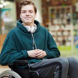 Dans la bibliothèque de l'école, un élève du secondaire en fauteuil roulant sourit pour la caméra.