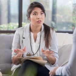 Une professionnelle de la santé mentale en milieu scolaire est assise sur un canapé, une planchette à pince sur les genoux. Elle est en train d'expliquer quelque chose à un élève.