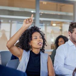 Un groupe de professionnels de la santé mentale en milieu scolaire écoutent une présentation. Une personne lève la main pour poser une question.