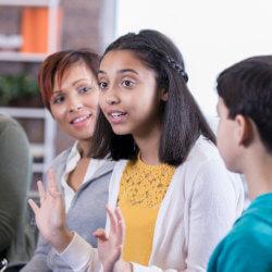 Des élèves et un membre du personnel sont assis dans un cercle sur des chaises. Ils participent à une discussion en groupe. Une fille est en train de parler. Les autres l'écoutent.