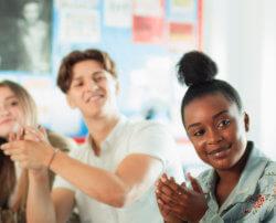 Des élèves du secondaire sont assis autour d'une table, en train d'applaudir un autre élève qui vient de terminer sa présentation.