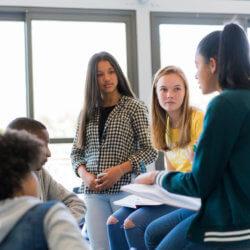 Un groupe d'élèves du secondaire prennent part à une discussion en salle de classe. Plusieurs élèves sont assis sur des pupitres, et d'autres sont assis sur des chaises. Quelques-uns tiennent des cahiers ouverts sur les genoux.